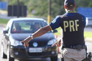 Policial rodoviário mandando carro parar.